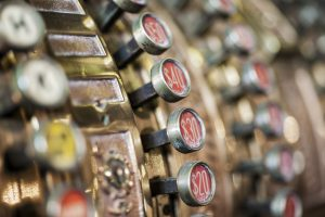 A close-up view of the keys on a vintage brass cash register.
