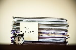 Traditional alarm clock in front of a stack of paper documents with handwritten tax time on a sticky note