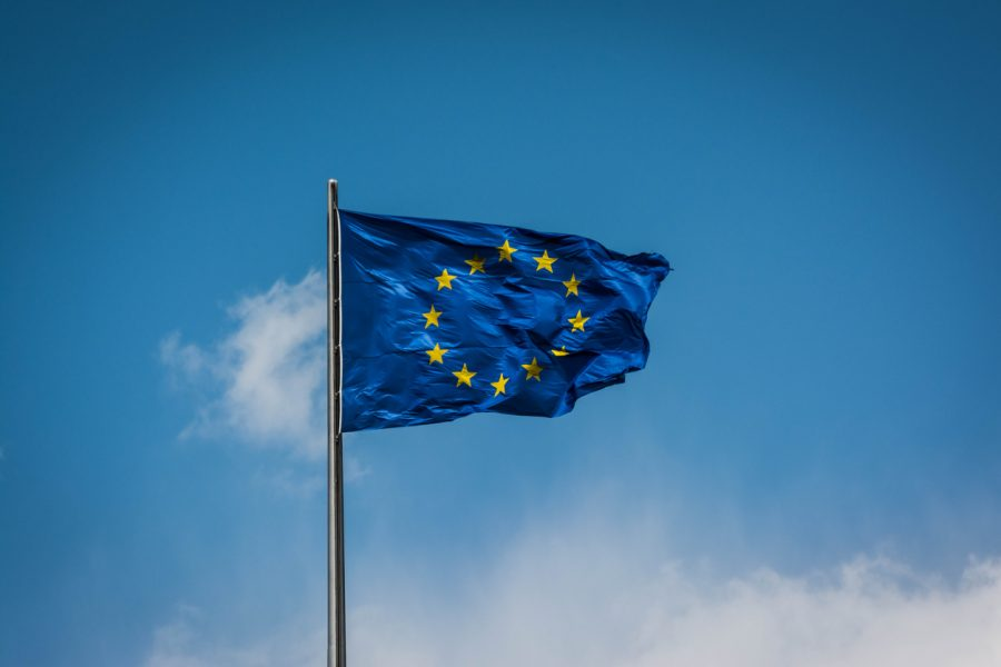 The European flag fluttering in the wind with a blue sky background.