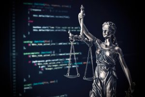 Justice statue with code on monitor device in background. programming code law crime justice internet statue themis concept